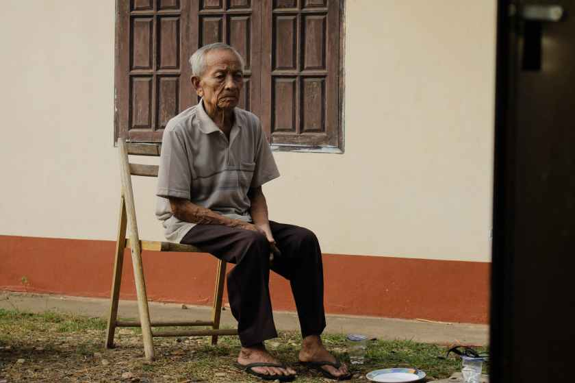 photo of elderly man sitting on wooden chair outside house